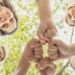 four women touching fists