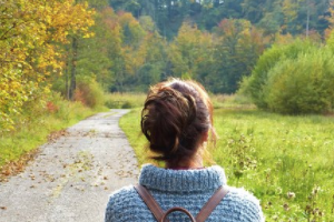 woman looking at forest path